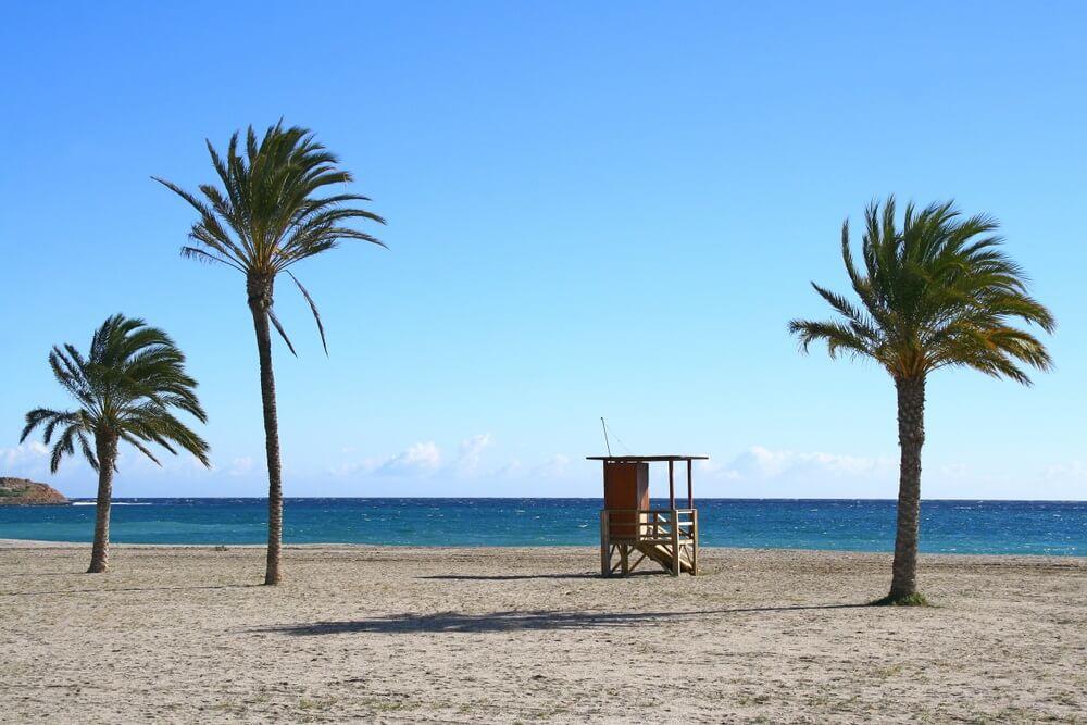 Het strand van Almeria, wit zand met een drietal palmbomen en een houtje hutje in het midden. Strakblauwe lucht.