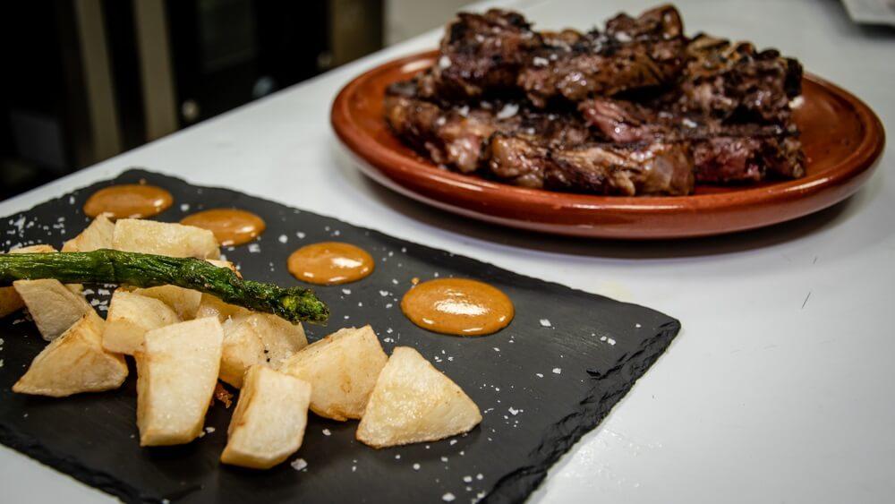 Een tweetal tapas, de een geserveerd op een grijze stenen plaat en de ander in een bruine schaaltje, beide op een witte tafel.