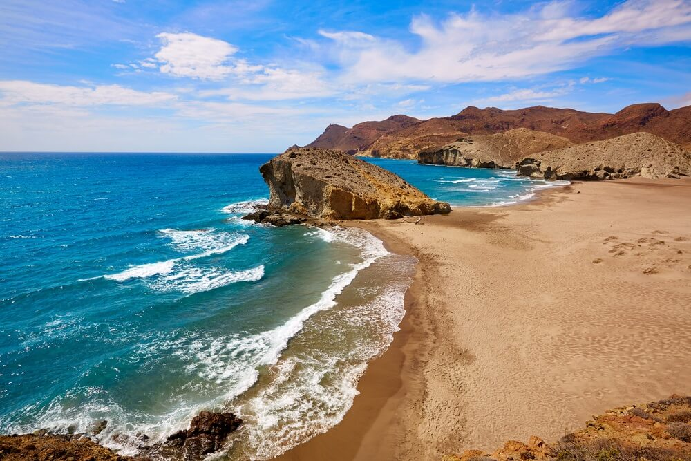 Prachtige strand bij Cabo de Gata Nationaal Park. Heuvels op de achtergrond en links azuurblauwe zee met witte golven. Blauwe lucht met enkele wolken.