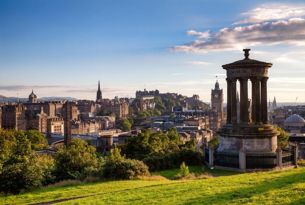 Edinburgh skyline gezien vanaf de Calton Hill met het Dugald Stewart Monument op de voorgrond.