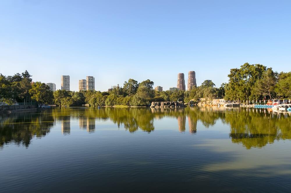 Uitzicht op het meer en wolkenkrabbers in Chapultepec park, Mexico stad. Strakblauwe lucht, groot meer op de voorgrond.