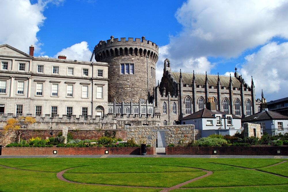 Het kasteel van Dublin. Groen grasveld daarvoor, blauwe lucht met enkele wolken in de lucht.
