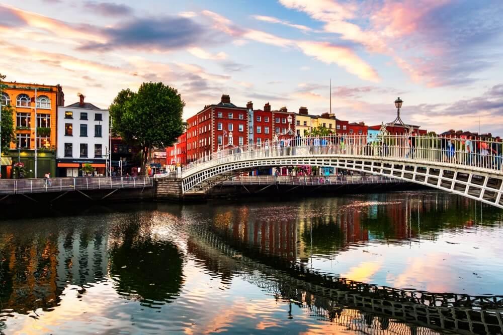 Dublin, Ierland. Nachtzicht van de beroemde verlichte Ha Penny Bridge in Dublin, Ierland bij zonsondergang