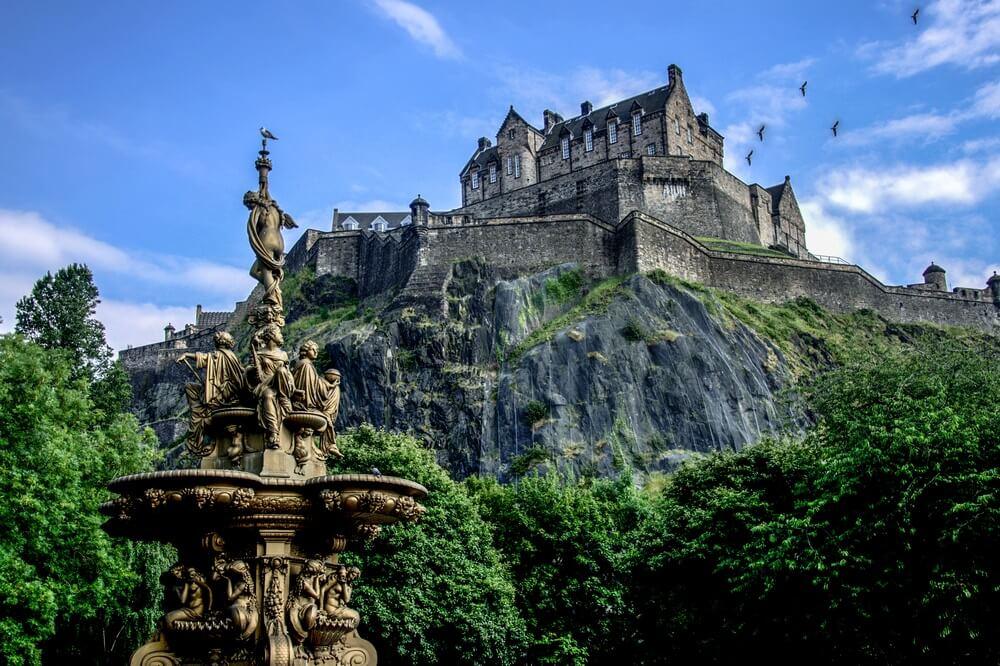 Het kasteel van Edinburg gelegen op een heuvel. Links daarvan 5 vogels. op de voorgrond een historische fontein. Blauwe lucht met enkele wolkjes.