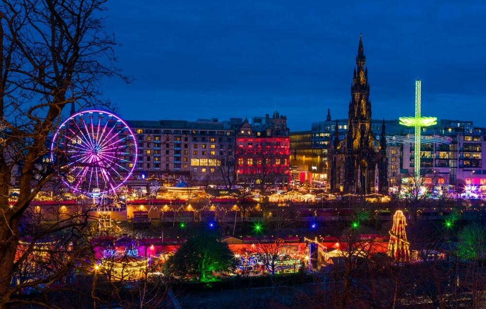 Kerst in Edinburgh bij schemering. Overal gekleurde lichtjes en kraampjes, verlicht reuzenrad en de kathedraal op de achtergrond.