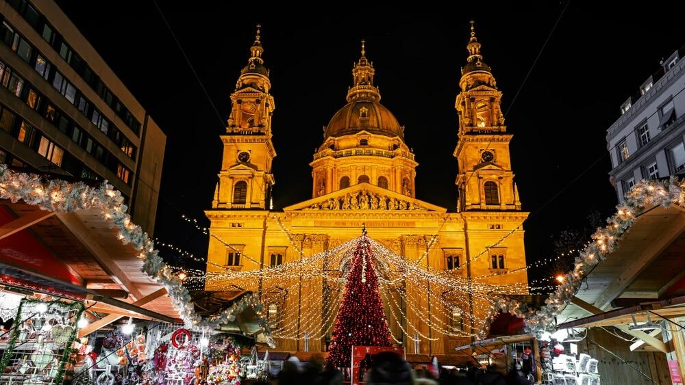 Kerstmarkt op het Vorosmarty-plein voor de Sint-Stefanus basiliek (vertaling: ik ben de manier waarop de waarheid en het leven) in de avondlichten - Boedapest, Hongarije.