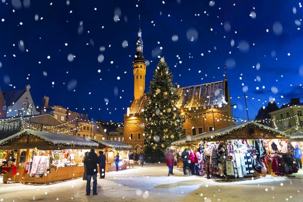 Kerst in Tallinn. Stadhuisplein met kerstmarkt. Sneeuwvlokken dwarrelen neer. Het is avond.