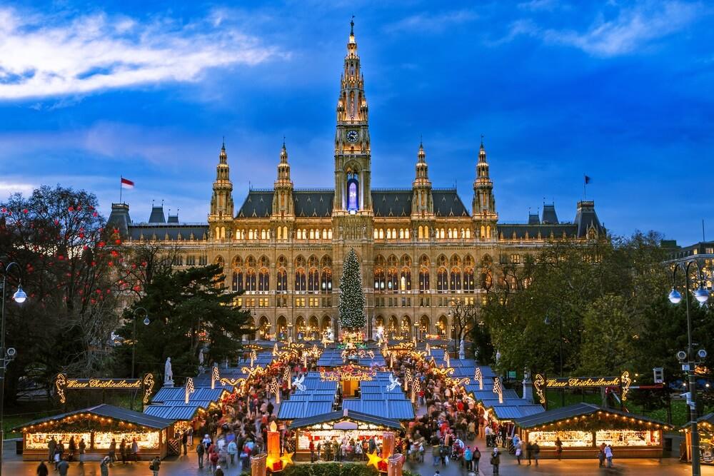 Kerstmarkt in Wenen bij schemering. Enorme paleis op de achtergrond. Bomen aan weerszijden en overal lichtjes.