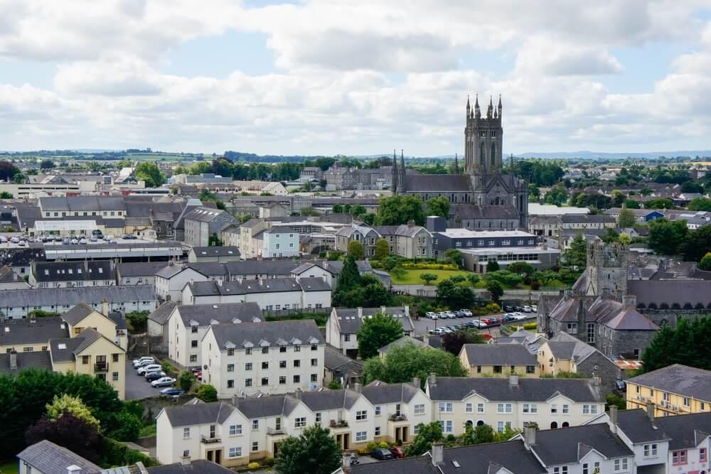 Uitzicht over de stad Kilkenny, Ierland, vanaf de ronde toren van de kathedraal van St. Canice met een mix van moderne en middeleeuwse architectuur onder een bewolkte hemel en de kathedraal van St. Mary die boven de stad uitkomt.