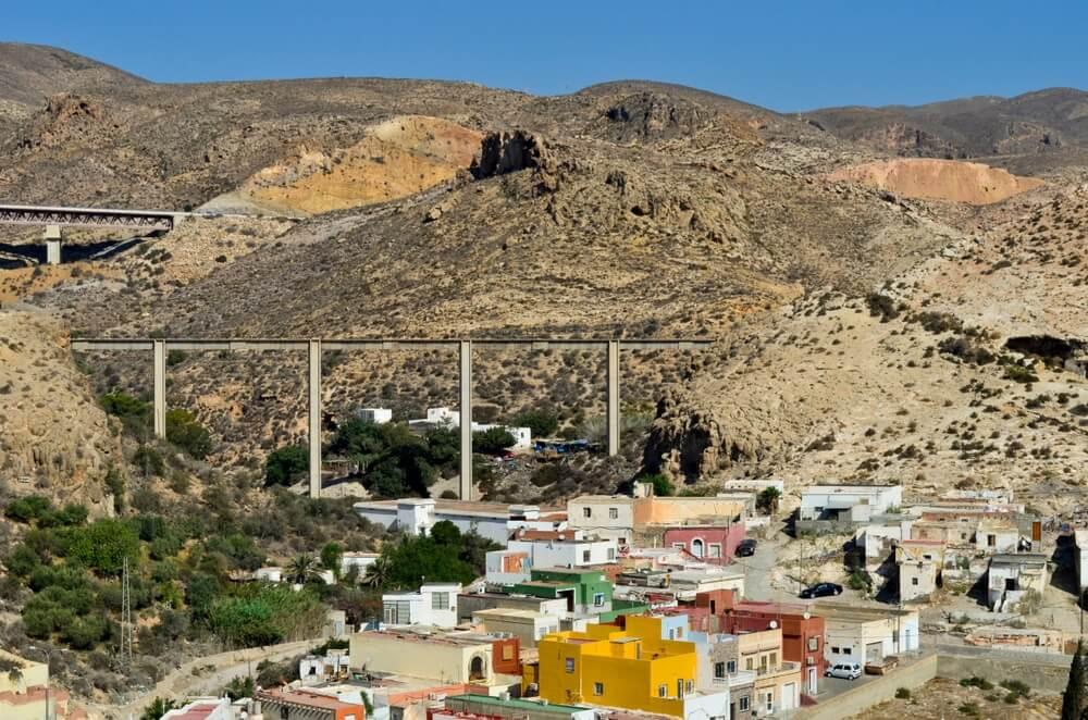 De La Cancha wijk in Almeria, gelegen tegen een dorre heuvel. Gekleurde huisjes en een paar groene bomen links daarvan.