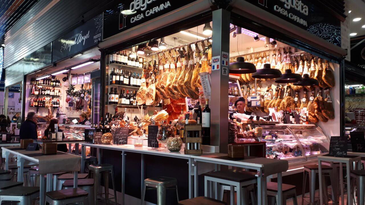 """San Augustin markt in Granada. Vlees kraampje met verse """"jamon"""" die aan een reling hangt. Klein barretje en tafeltjes met stoelen daaraan."""