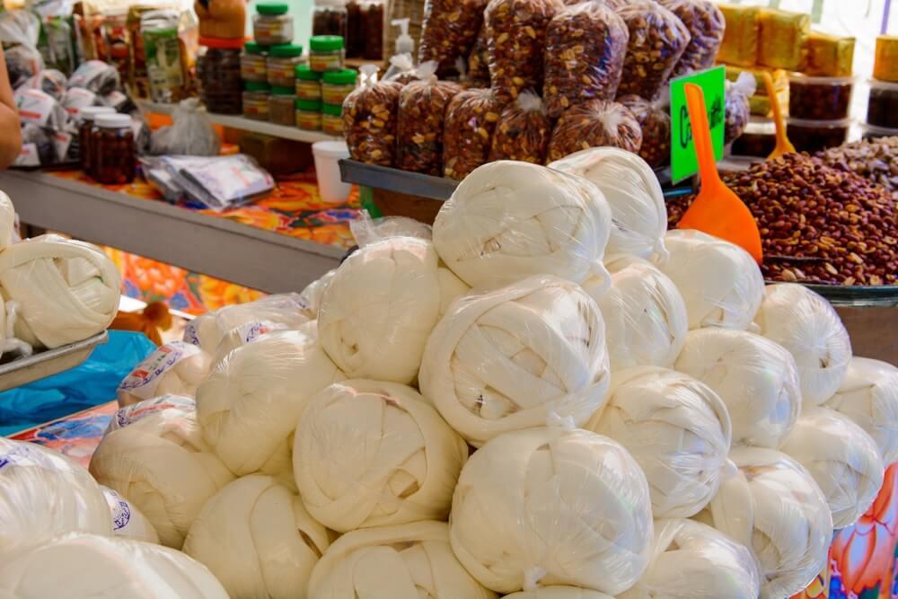 Verschillende etenswaren op een markt in Oaxaca, Mexico. Grote bollen kaas, plastic zakjes met nootjes, potjes ingemaakte groenten etc.