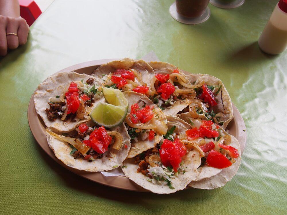 Een bord vol verse Mexicaanse taco's met vlees, ui en salsa.