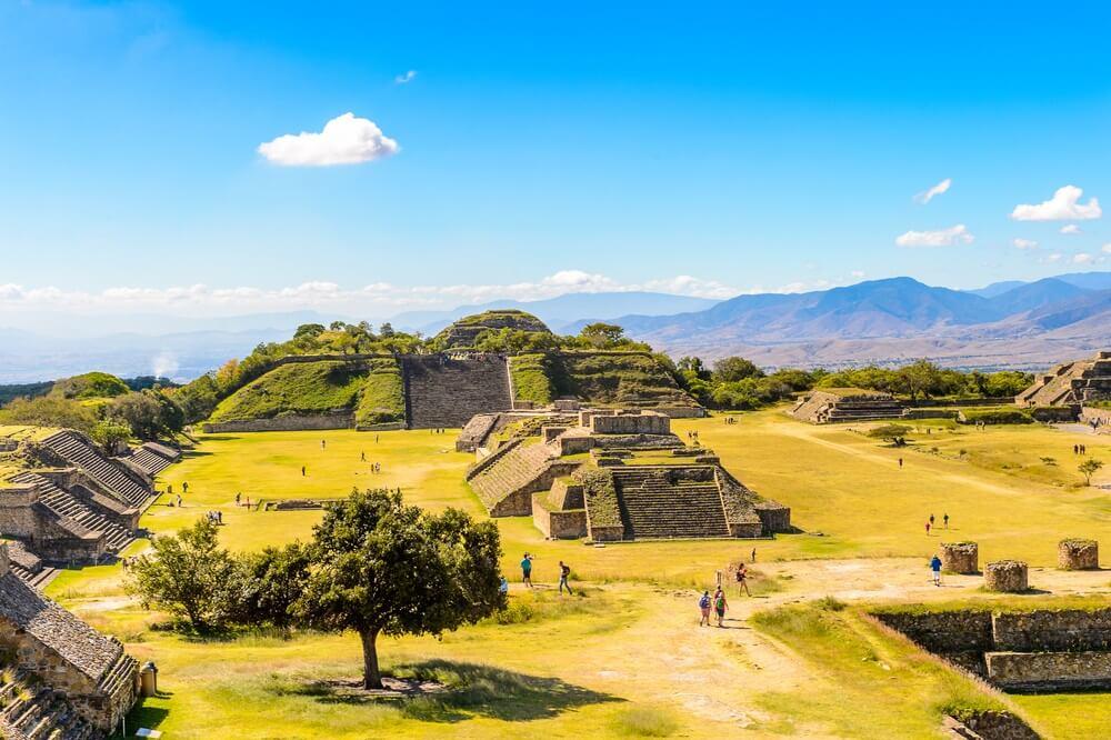 Uitzicht over de Monte Alban en oude ruïnes nabij Oaxaca, Mexico. Blauwe lucht en heuvels op de achtergrond.