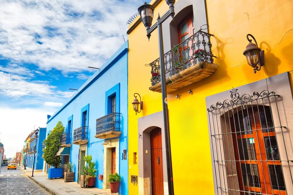 Straatje met geel en blauw gekleurde huisjes in Oaxaca stad.