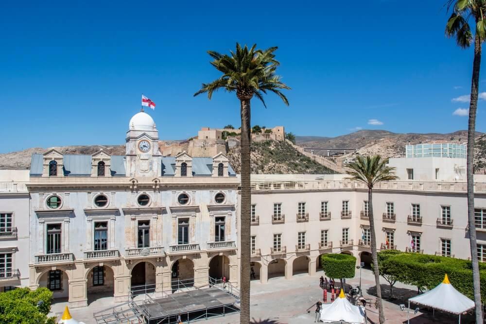 Uitzicht op het centrale plein van Almeria, in het historische centrum. Grote palmboom in het midden, heuvels en blauwe lucht op de achtergrond,