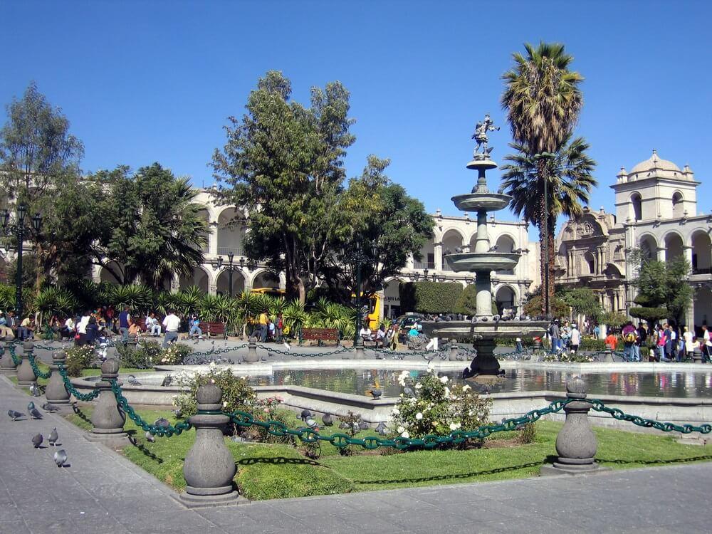 Plaza de las Armas in Arequipa, Peru. Blauwe lucht, mensen zitten op bankjes. Duiven op de grond.