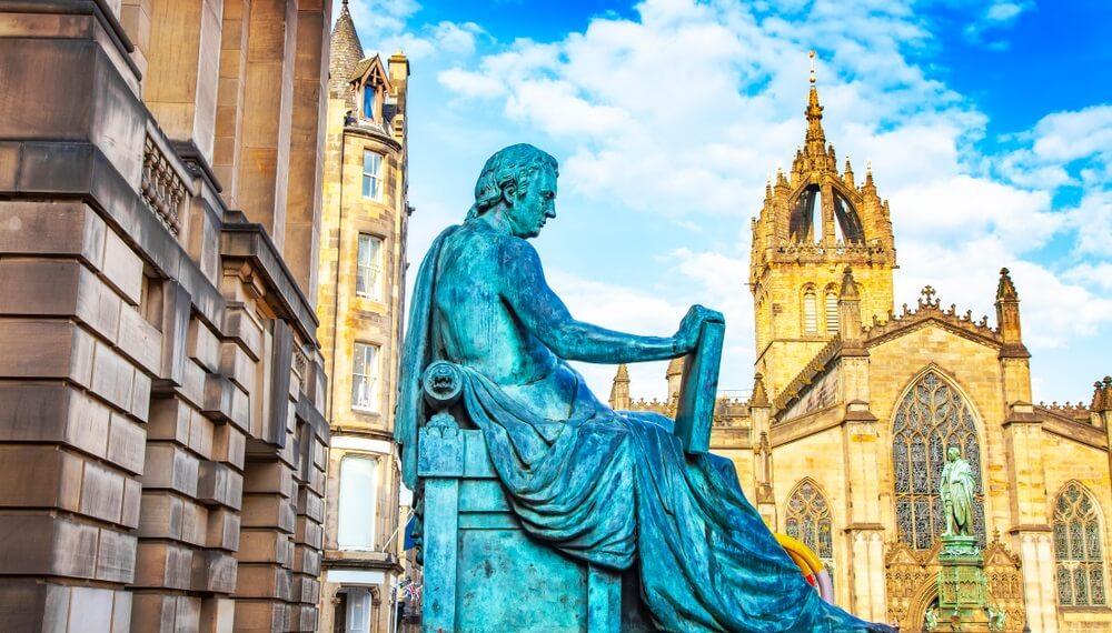 Royal Mile straat in Edinburgh. Standbeeld in het midden van een man die op een stoel zit. Rechts daarnaast kathedraal van Edinburgh.