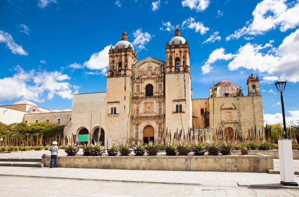 De Santo Domingo kerk in Oaxaca. Links daarvoor een man met zijn rug naar de camera toe. Blauwe lucht met enkele wolkjes.