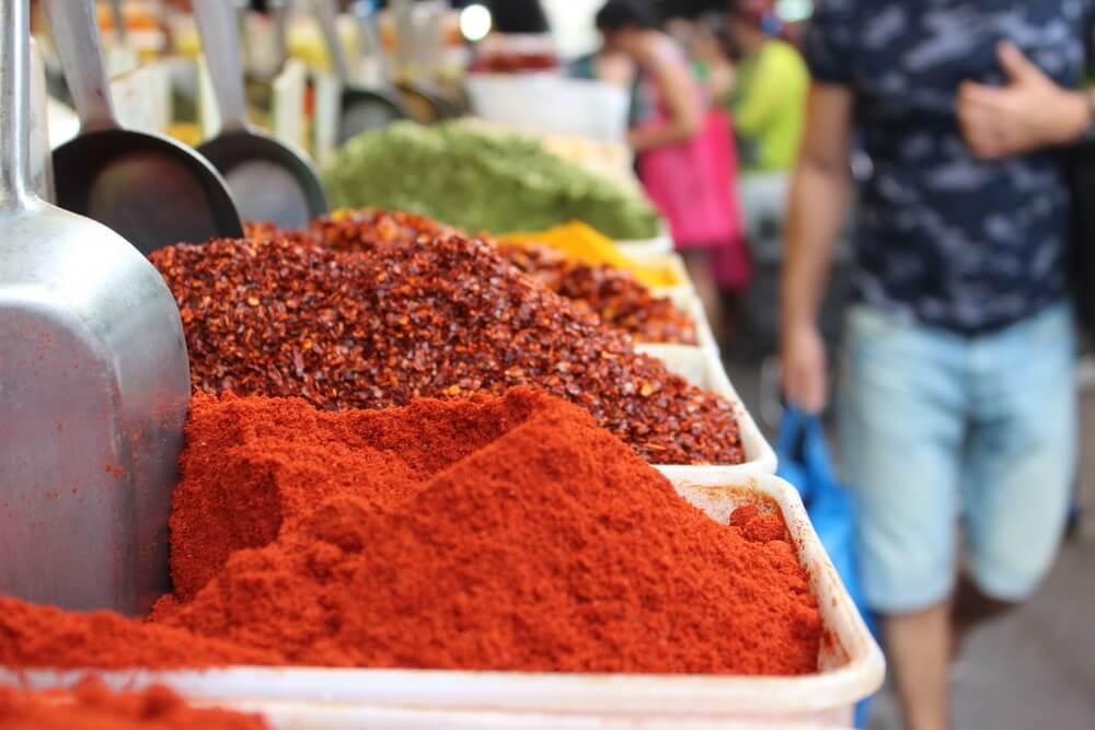 Gekleurde kruiden en specerijen op de Carmel markt in Tel Aviv. Links lopen een aantal mensen, alleen de romp zichtbaar en blurry.