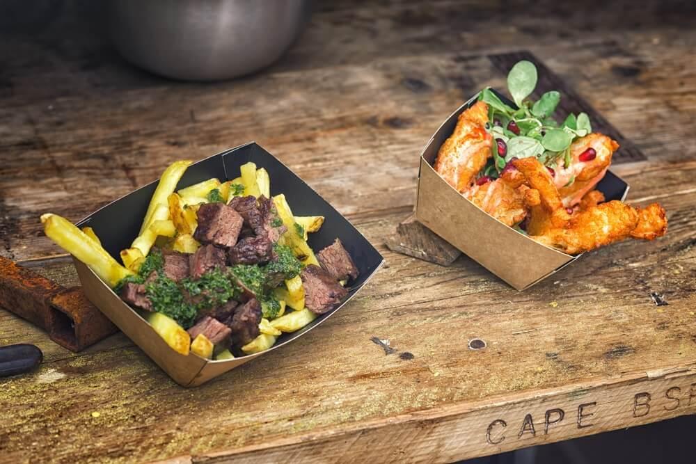 Close-up op Verscheurd rundvlees met friet en kip met Spaanse pepers. Straatvoedselmarkt in Edinburgh. Houten tafel.