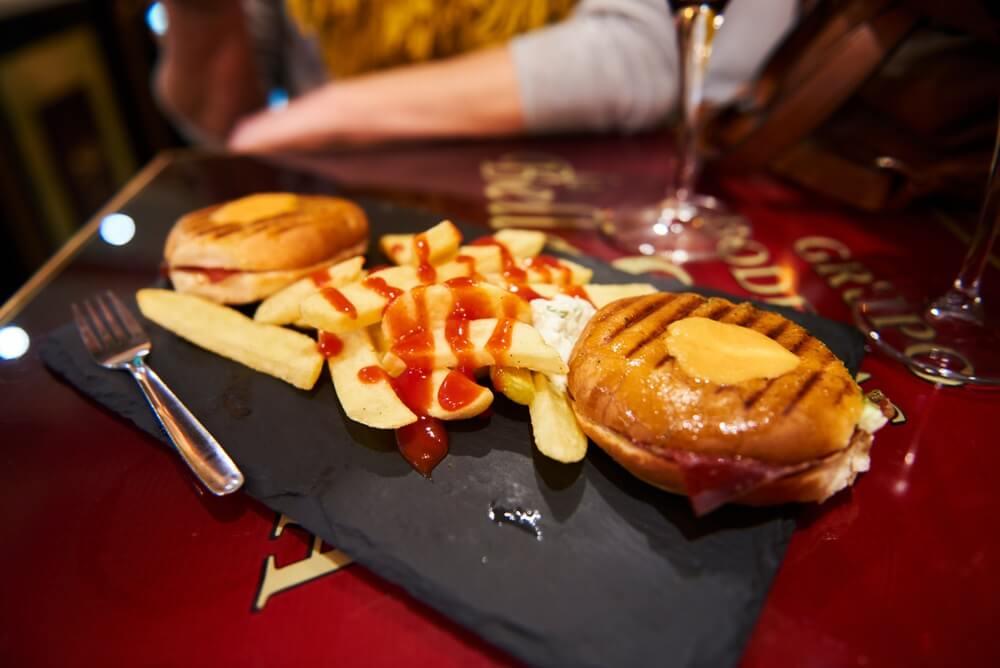 Tapas op een stenen plankje op een tafel in Granada. 2 broodjes met jamon, frietjes met saus en 2 wijnglazen op de achtergrond.