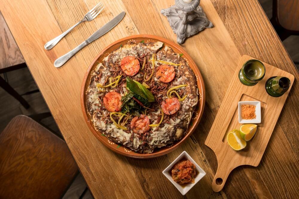 Traditioneel eten in Oaxaca stad: en bruine schaal met tlayuda erin geserveerd op een houten fatel. Mes en vork daarnaast en een houten snijplankje met 2 partjes sinaasappel en een bakje met kruiden.