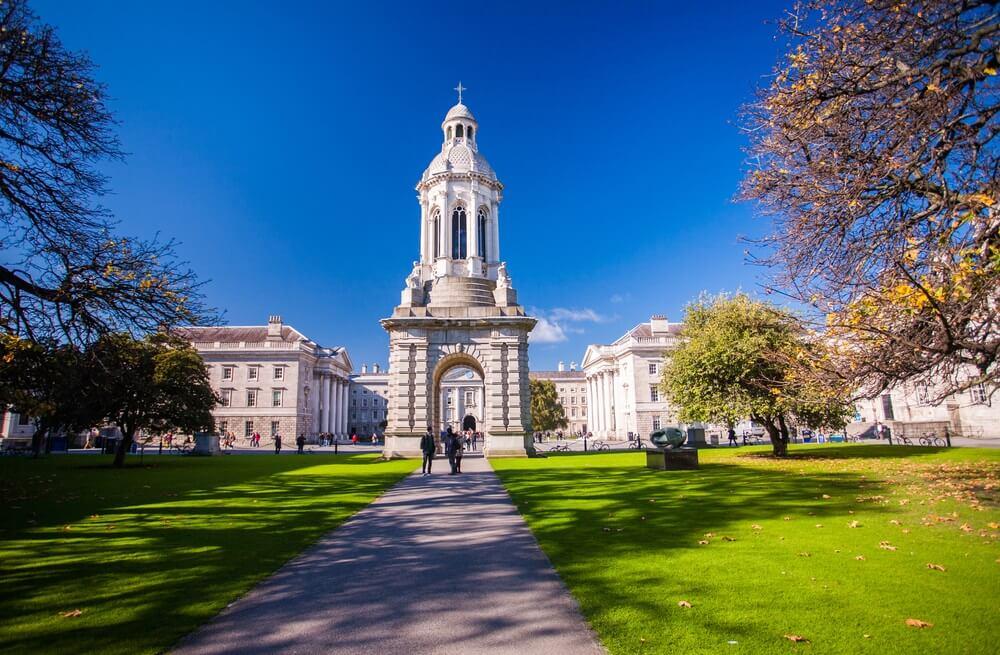Trinity College Dublin. prachtig wit gebouw in een groen park met een looppad in het midden en grasveld aan weerszijden. Strakblauwe lucht.