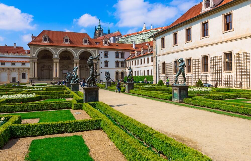 De Koninklijke tuin in de Praagse Burcht. Netjes aangelegde lanen met groene coniferen en een lang looppad.