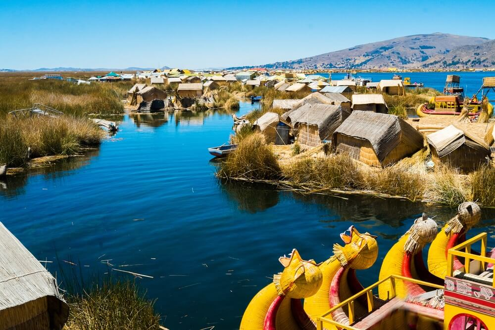 Uitzicht op Uros drijvende eilanden met typische boten, Puno, Peru