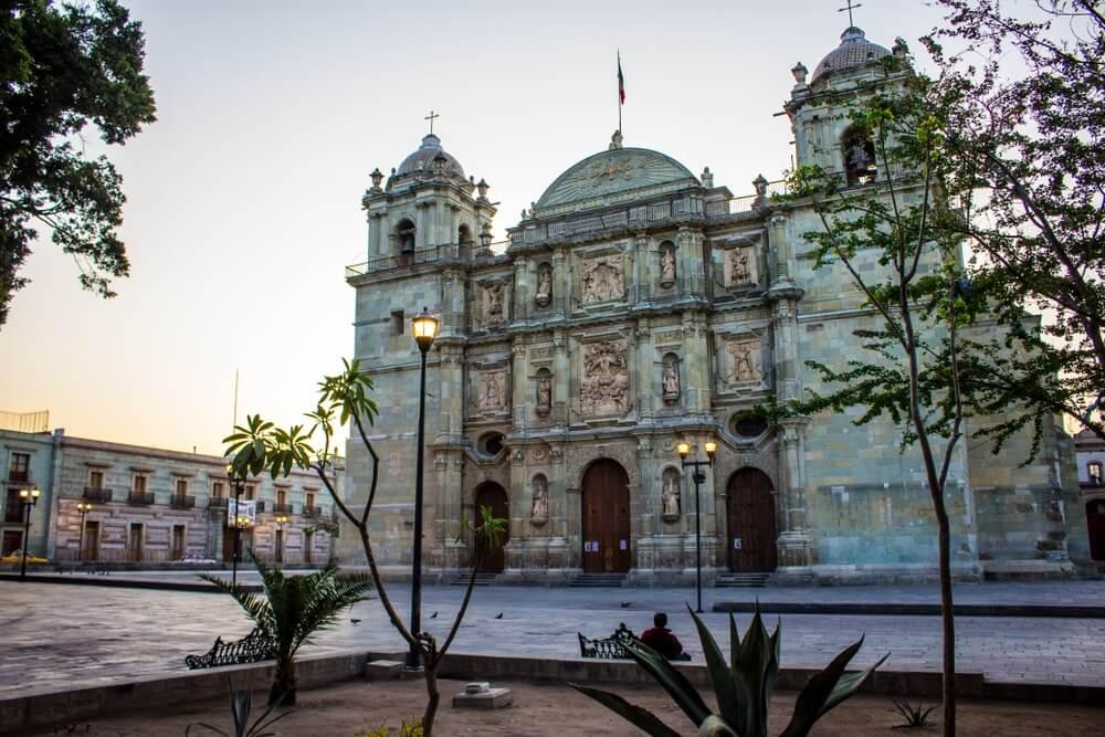 """Het centrale plein """"Zocalo"""" in Oaxaca stad. Oude kathedraal op de achtergrond en enkele lantaarnpalen met licht bij schemering."""