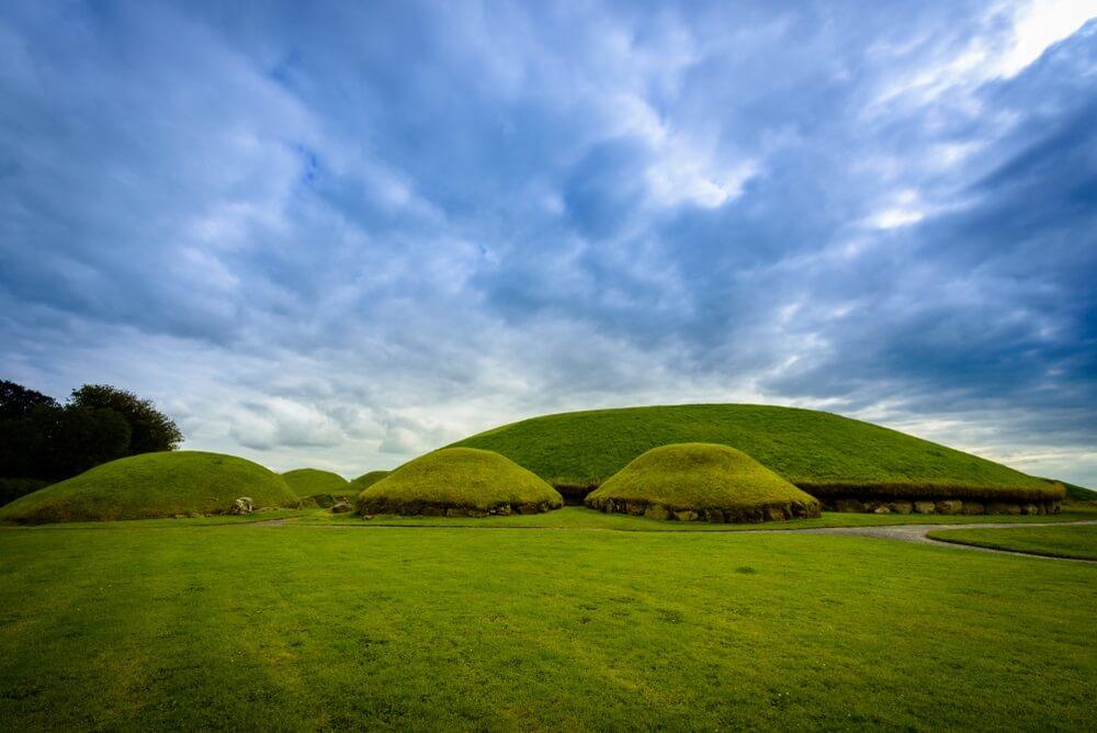 Groene heuvels, oftewel doorgangsgraven in het historische Bru na Boinne in Ierland, nabij Dublin. Grijs/blauwe lucht op de achtergrond.