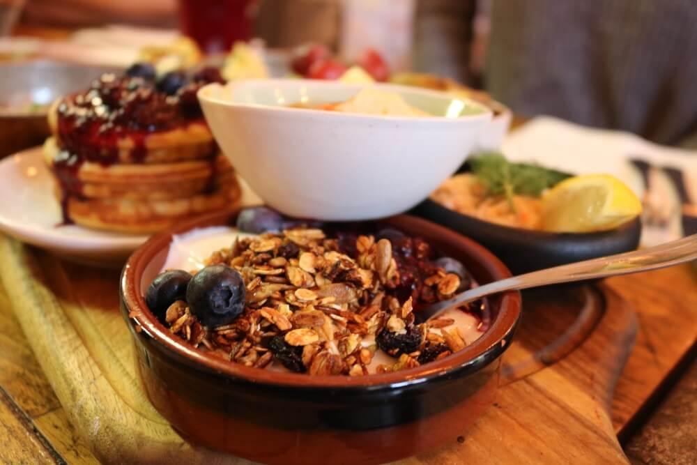 Een houten plank vol met brunchgerechten in Kopenhagen. Bakje met muesli, yoghurt en bessen op de voorgrond.