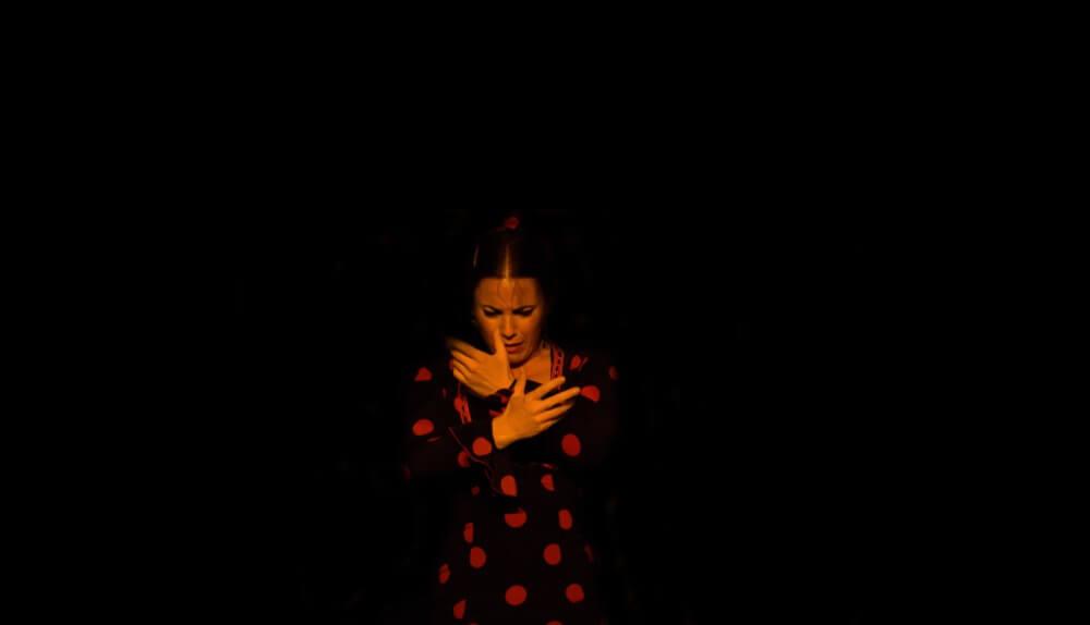 Vrouw danst de flamenco en draagt een zwarte jurk met rode stippen. Zwarte achtergrond.