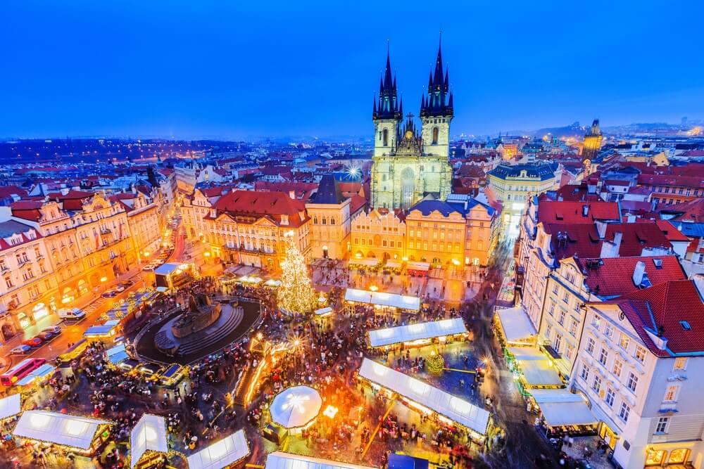 Praag, Tsjechië. Kerstmarkt op het oude stadsplein bij schemering. Overal lichtjes.