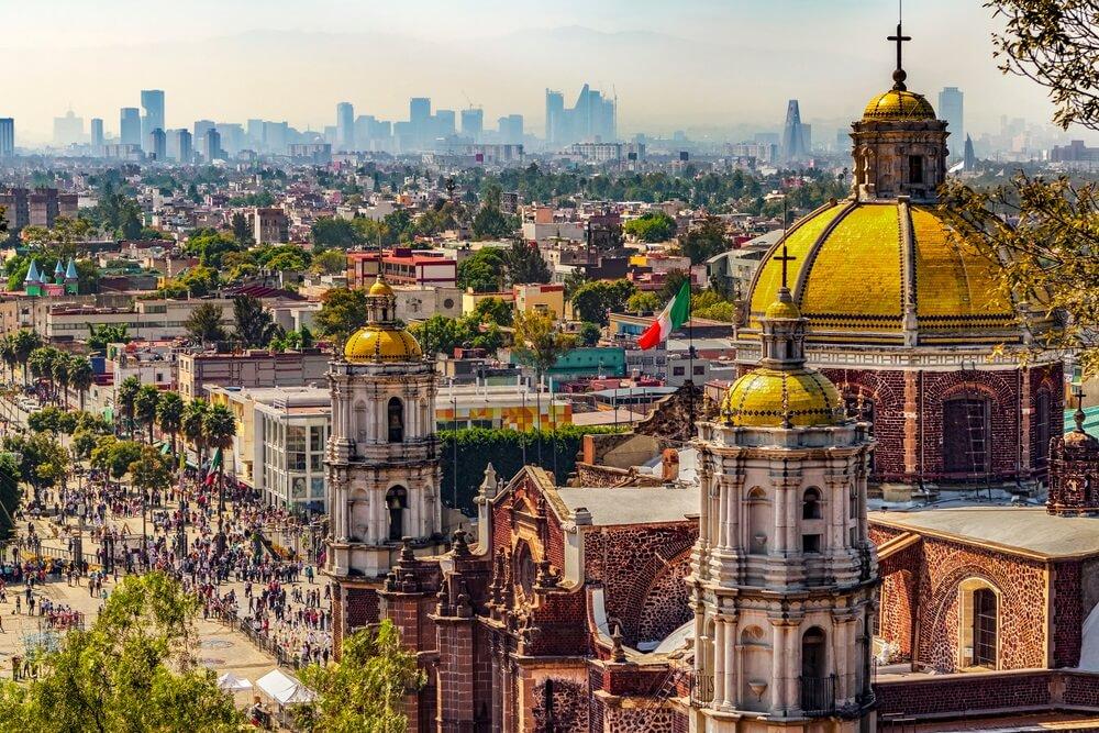 In Mexico. Basiliek van Onze-Lieve-Vrouw van Guadalupe. Cupola's van de oude basiliek en stadsgezicht van Mexico-Stad op de verre skyline.