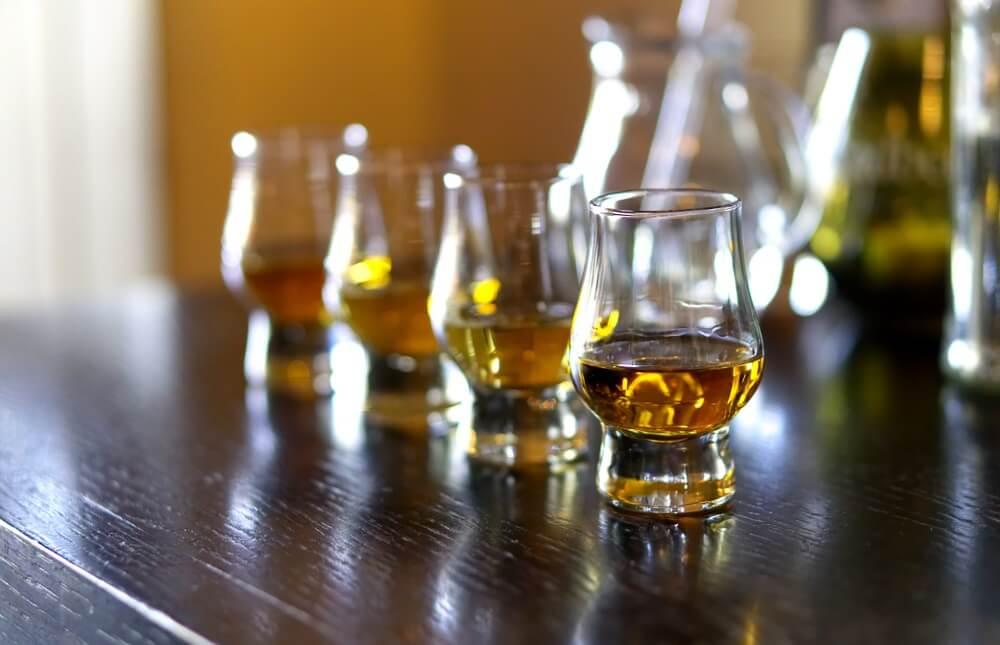 Vier kleine glaasjes met Schotse whisky daarin. Geserveerd op een houten tafel.