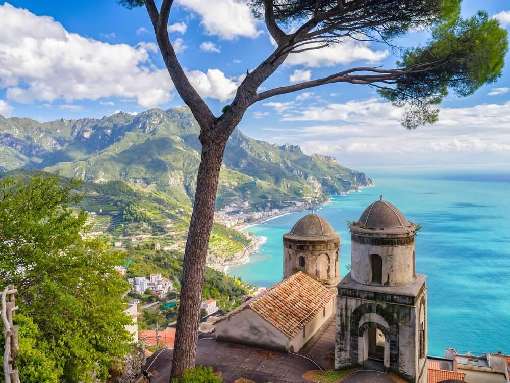 Amalfikust Italië vanaf een berg. Kerkje op de voorgrond en groene bergen, blauwe zee in de verte.