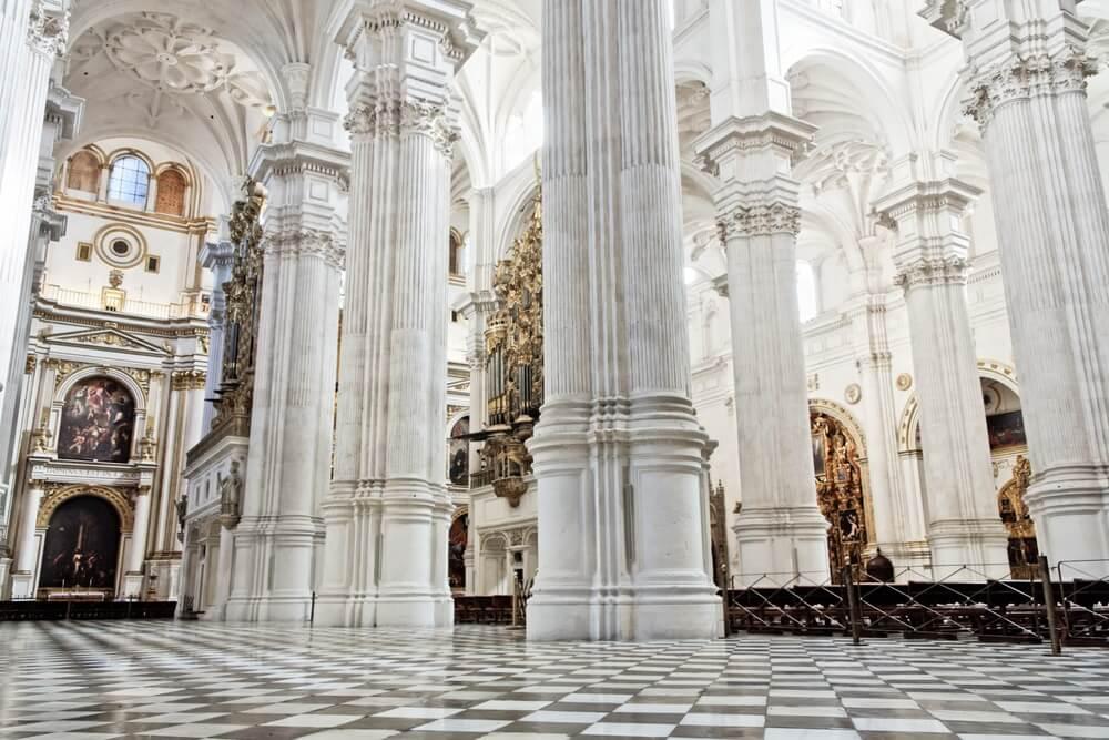 Kathedraal van Granada van binnen. Hoge, witte pilaren en een zwart witte tegelvloer.