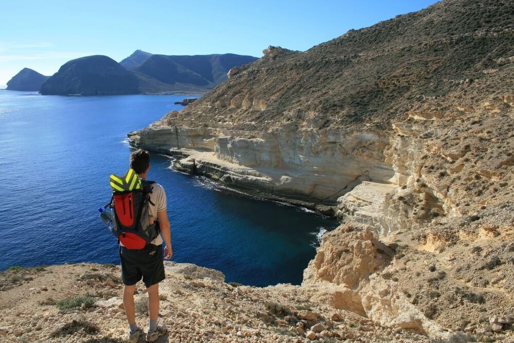 Een wandelaar staat met zijn rug en backpack naar de camera en kijkt uit over de kust en de rotsachtige kliffen in Cabo de Gata natuurpark, Spanje