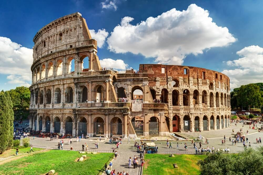 Colosseum in Rome, Italië. Het oude Romeinse Colosseum is een van de belangrijkste toeristische attracties in Europa. Mensen bezoeken het beroemde Colosseum in Roma centrum. Schilderachtig uitzicht op de ruïnes van het Colosseum in de zomer.