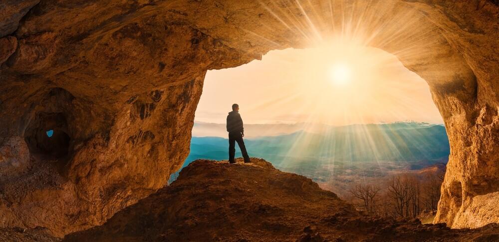 Prachtige prachtige zonsondergang. Bergen in Kaukasus. Uniek landschap grootzeil. Silhouet van een man. Oude grot. Actieve sport en hobby. Spelende achtergrond.
