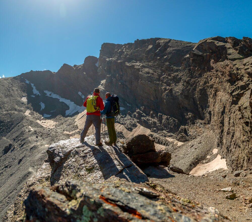 Twee anonieme reizigers die zich op ruwe rots bevinden en schilderachtig uitzicht op majestueuze bergen in Sierra Nevada, Granada, Spanje bewonderen.