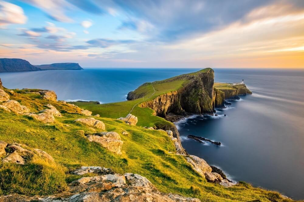 Neist Point vuurtoren op het eiland Skye badend in gouden licht van de ondergaande zon.
