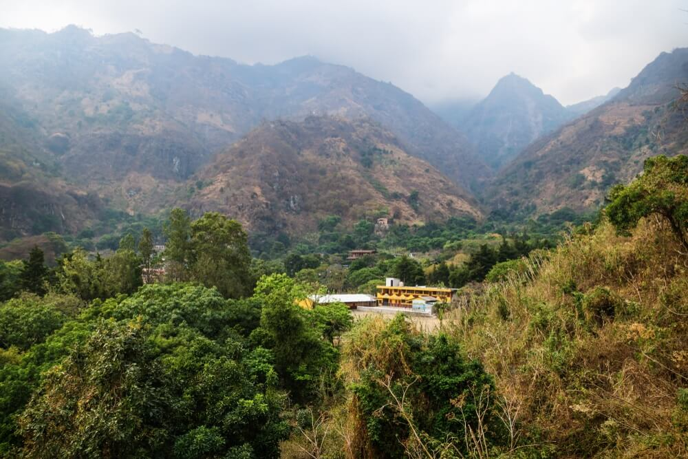 School in de vallei van het dorp Jaibalito langs het meer Atitlan met mistige vulkanische bergen, Guatemala.