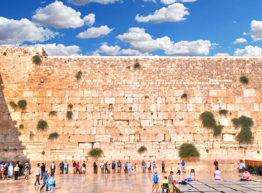 Klaagmuur in Jerusalem. mensen die voor de muur staan te bidden. Blauwe lucht me wolkjes daarboven.
