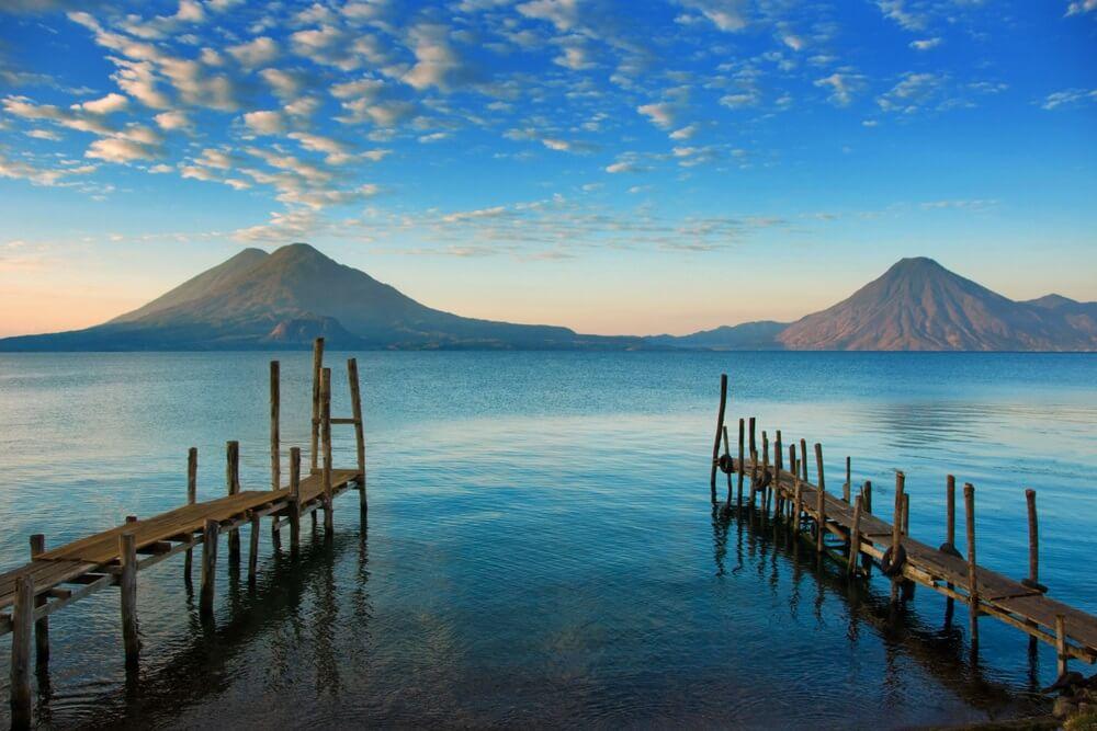 Kalm blauw meer Atitlan Guatemala bij Ochtendzonsopgang. Rustige kustdokkenmening met vulkanen op Achtergrond