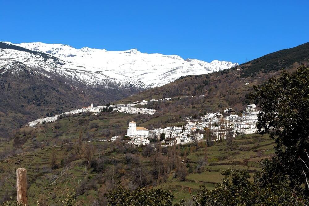 Beeld van de stad met Capileira en met sneeuw bedekte bergen aan de achterzijde, Bubion, Las Alpujarras, de provincie Granada, Andalusië, Spanje, West-Europa.