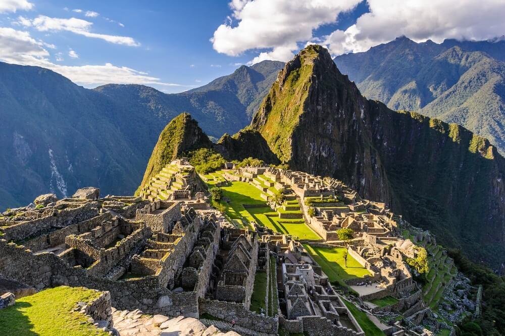 Uitzicht over Machu Picchu, Peru. Hoge bergen op de achtergrond en blauwe lucht met enkele wolken.