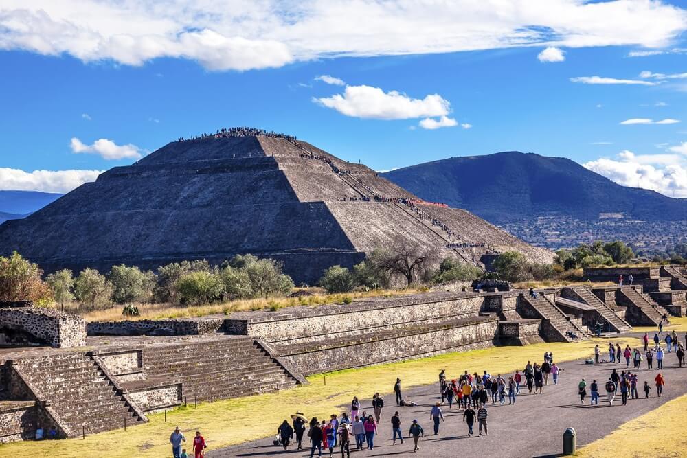 Mensen lopen rond in Teotihuacán over de lange Calle de los Muertos, naast de Piramide van de Zon. blauwe lucht met enkele wolkjes.